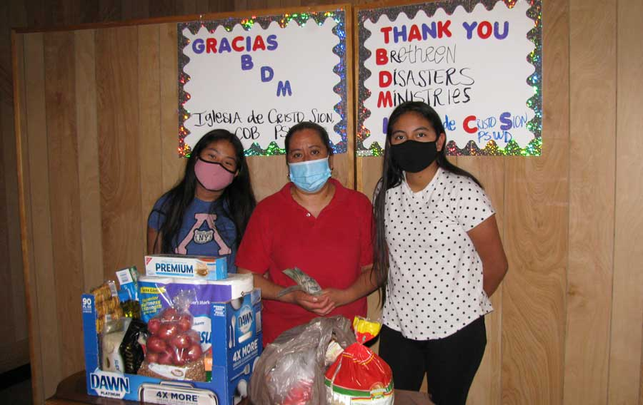 """Three women wearing masks standing behind a table with food. A sign says """"Gracias BDM"""""""