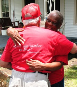 Brethren Disaster Ministries volunteer in red shirt hugging a woman in front of a porch