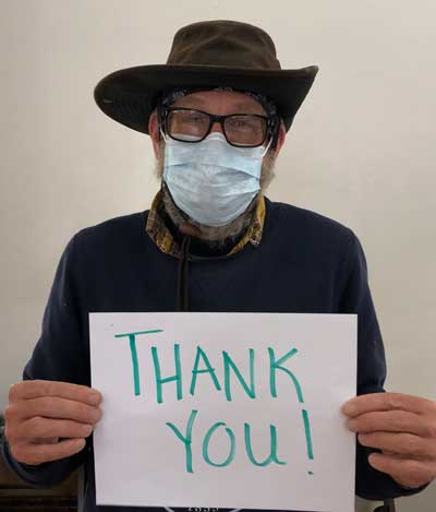 """Man wearing hat holding sign that says """"THANK YOU!"""""""