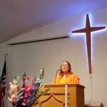 Beth Nonemaker preaching with lighted cross behind her