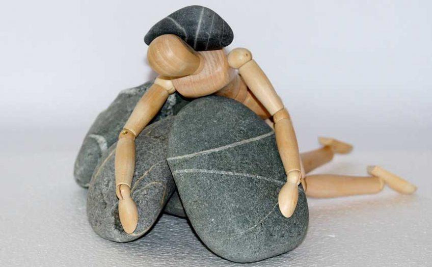 Wooden mannequin under rocks