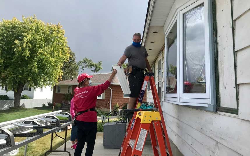 A volunteer in a red Brethren Disaster Ministries shirt and hat hands a board to a volunteer on a ladder.