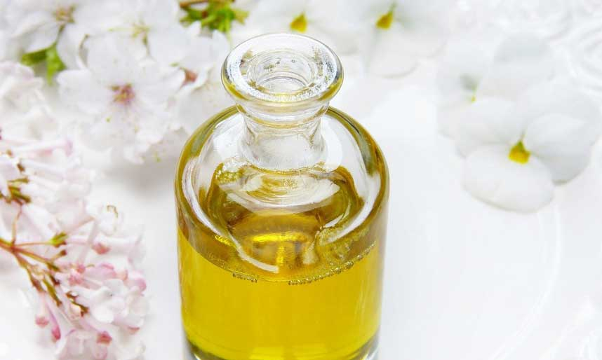 Glass jar of oil with flowers surrounding it