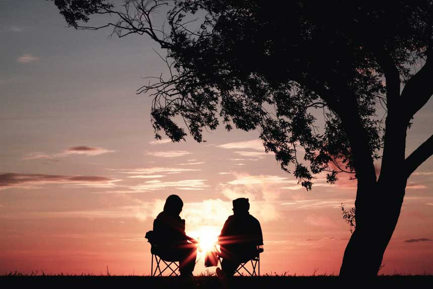 Two people sitting on chairs next to a tree, silhouetted against a pink sky and low sun