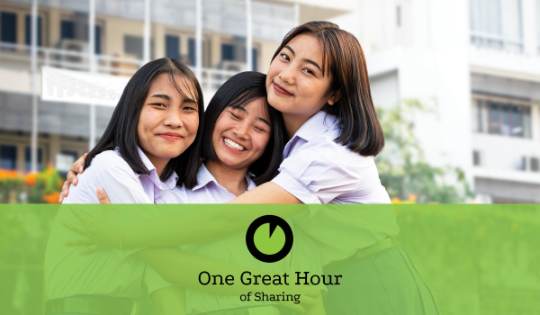 Three women hugging each other and smiling, One Great Hour of Sharing logo