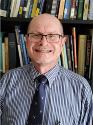 Jim Benedict smiling in front of a bookshelf