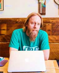 Ryan Braught sitting at a wooden booth with a laptop