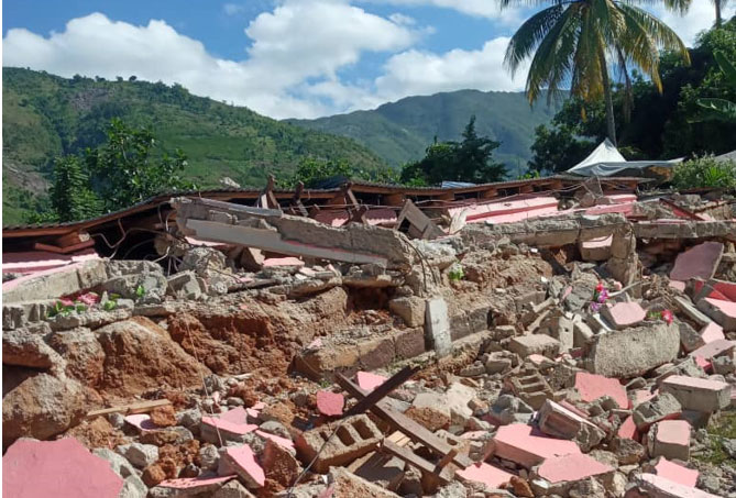 Broken building and rubble in front of a green mountain
