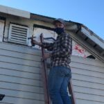 Man in hat, face covering, flannel shirt, and jeans hammering on a damaged house