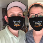 "Two people wearing masks that say ""Peacefully, Simply, Not so close Together"""
