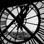 Black and white photo of city view through large clock